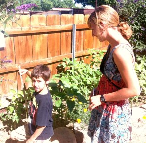 A significant component of the AmeriCorps Partner's role is in community education. Here, Elise helps a 3rd grader measure sunflowers planted by his class in the ESLT garden.