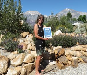 Our first certified gardener, Margy Marshall, posing in front of her garden.